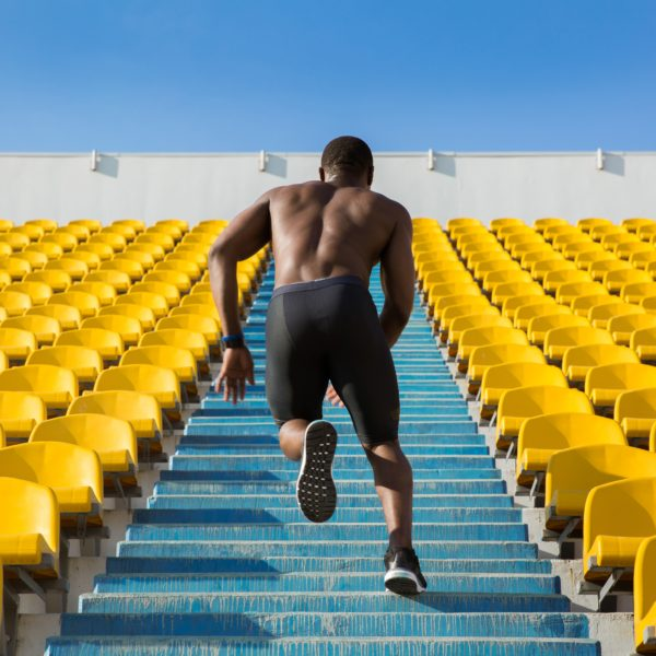 Back view of a sportsman doing speed exercise for muscles on the stairs at the stadium